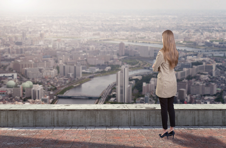A businesswoman standing on roof looking at city