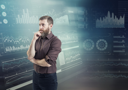 A businessman thinking standing against an abstract financial charts on the background