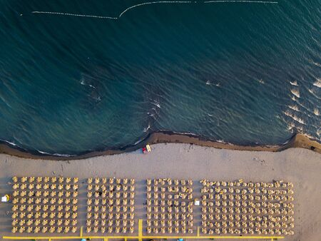 Aerial view of sandy beach with yellow sunbeds and wooden umbrellas at sunset 写真素材