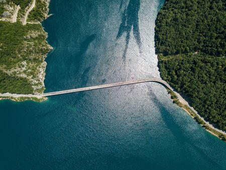 Aerial footage a car driving over a bridge on Piva Lake Banco de Imagens