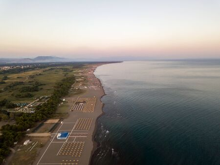 Aerial view of sandy beach with yellow sunbeds and wooden umbrellas at sunset Banco de Imagens