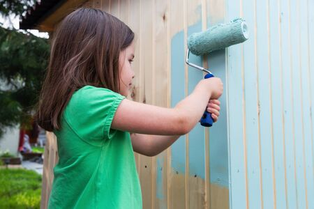 Young girl painting little wooden house with a roller