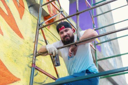 Graffiti artist painting with aerosol spray bottle