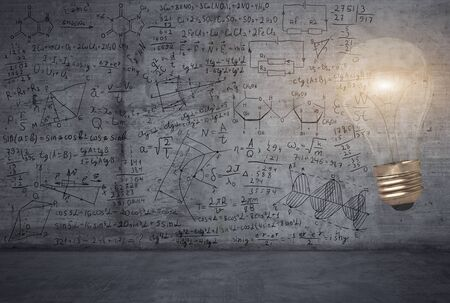 A bright light bulb against the background with maths and science sketches on a wall Banco de Imagens