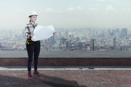 Female engineer holding construction plans standing on the roof top above a city Banco de Imagens