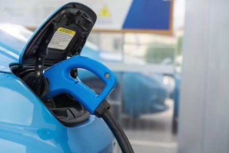 A man charging his electric car at charging station Banco de Imagens