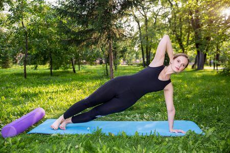 Beautiful woman doing Pilates in the green park Banco de Imagens