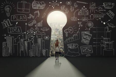 Vue arrière d'une femme d'affaires contre un mur noir avec trou de serrure Banque d'images
