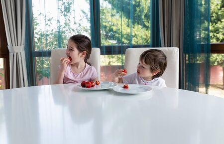 Cute children eating fresh ripe strawberries at home Standard-Bild - 131659638