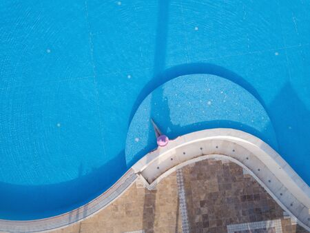 Young woman sunbathing in a swimming pool