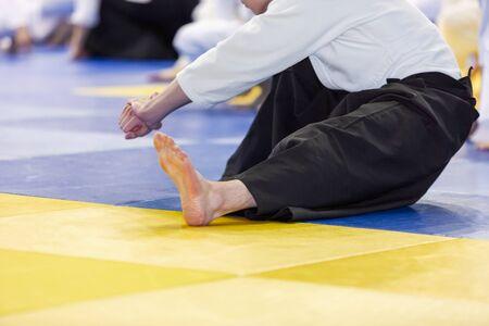 People in kimono warming up on tatami on martial arts training seminar Standard-Bild - 131659649