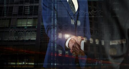 Business partners shaking hands on background with charts Standard-Bild - 131659923