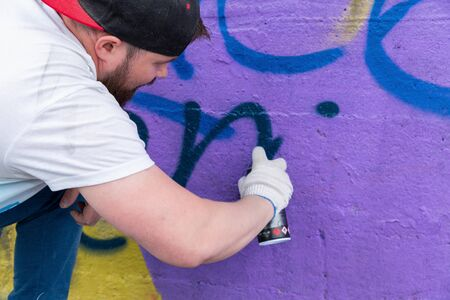 Graffiti artist painting with aerosol spray bottle Standard-Bild - 131659411