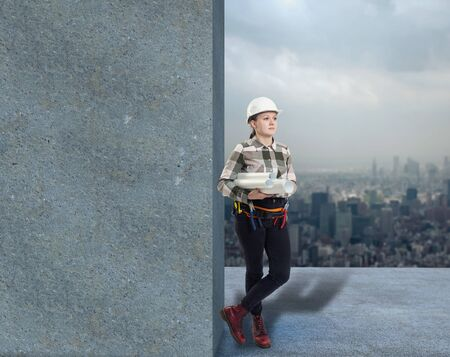 Female construction worker holding plans, leaning on blank wall Standard-Bild - 132186622