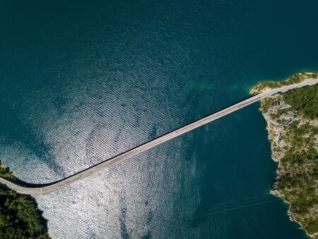 Aerial footage a car driving over a bridge on Piva Lake 写真素材
