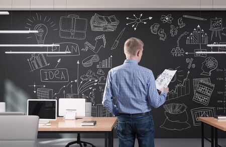 Young businessman in modern office with creative business strategy sketch drawn on a wall Zdjęcie Seryjne