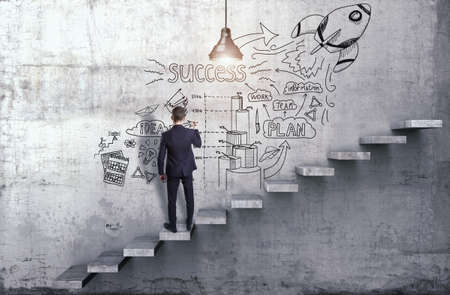 A businessman drawing the creative business strategy on a concrete wall with steps in it