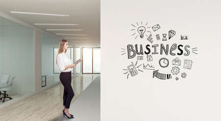 A businesswoman standing in modern office with creative business strategy sketch drawn on white wall