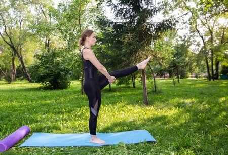 Beautiful woman doing Pilates in the green park Foto de archivo
