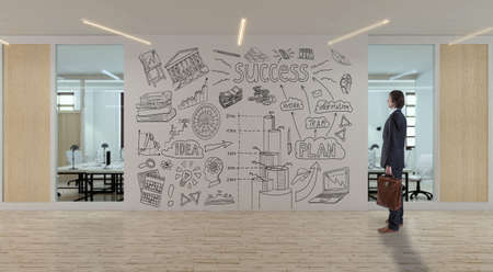 A businessman with a briefcase looks at the business sketch drawn on the wall in a modern office Foto de archivo