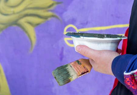Graffiti artist painting street art with paint brush
