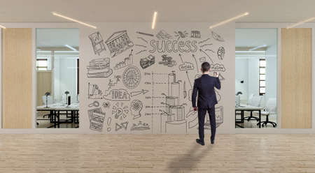 A businessman standing in modern office with creative business strategy sketch drawn on white wall Foto de archivo