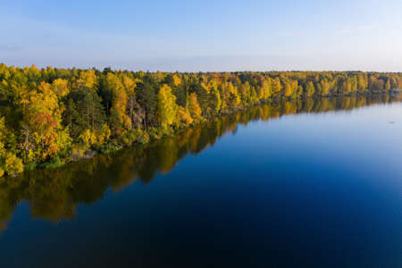Aerial top view of beautiful lake surrounded by colorful forest in autumn Standard-Bild