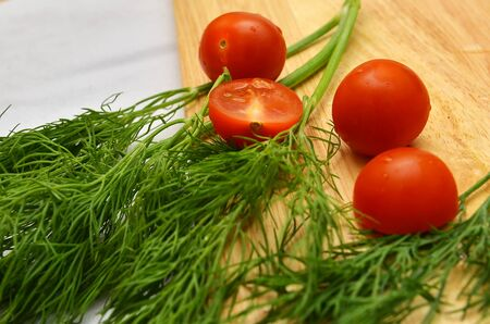 sprigs: on the board are cherii tomatoes and green sprigs of fresh dill