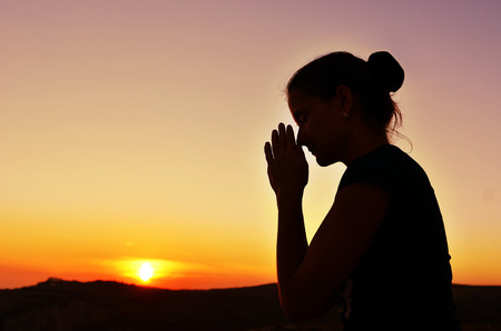 Girl folded her hands in prayer. Beautiful sunset. Colorful sky. Tenderness and serenity