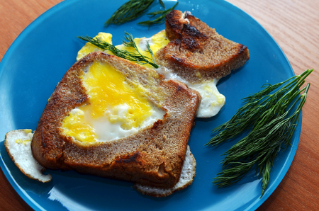 black bread: scrambled eggs, made in a piece of black bread. The bread is cut into a heart. Tasty breakfast for loved ones