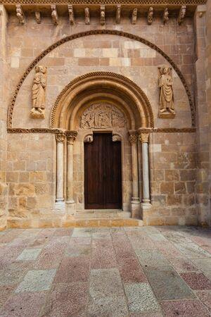Puerta de estilo románico con el tímpano esculpido llamado Puerta del Cordero en la Real Colegiata de San Isidoro en el siglo X en León España Foto de archivo - 30468330