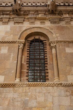 Excelente pieza de ventana de arte románico con la protección forjado fina en la pared lateral de la colegiata de San Isidoro en León, España Foto de archivo - 30468369