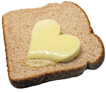 melts: Butter heart melts on a slice of bread Stock Photo