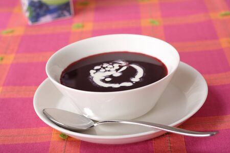 Bowl of sweet blueberry soup with cream