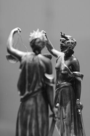 tribunal: Old bronze statue of Justice in front of mirror