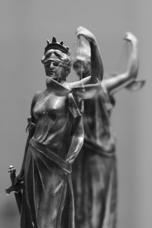 small sword: Old bronze statue of Justice in front of mirror