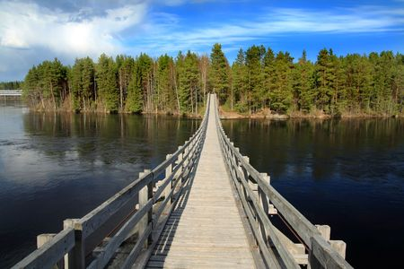 Suspended wooden bridge over a river in Finland