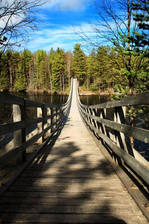Suspended wooden bridge over a river in Finland photo