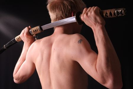 sword: Closeup of man holding samurai sword in dramatic studio light Stock Photo