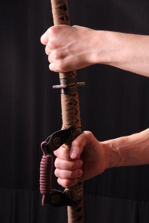 swordsmanship: Closeup of man holding samurai sword in dramatic studio light Stock Photo