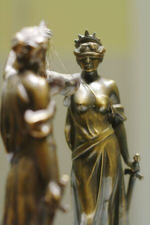 Old bronze statue of Justice in front of mirror