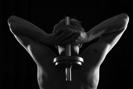 testosterone: Man training with weight in dramatic studio light