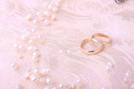 rings and pearls on satin cushion photo