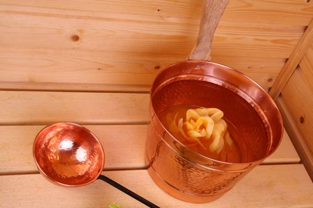 perspire: Bucket with water inside a Finnish sauna Stock Photo