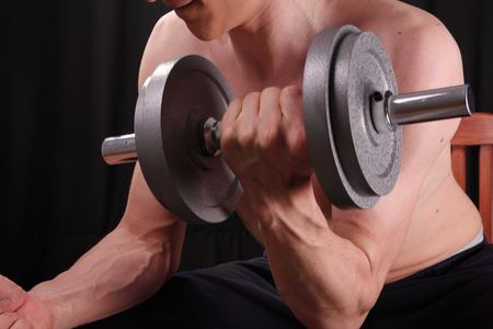 Man training with weight in dramatic studio light