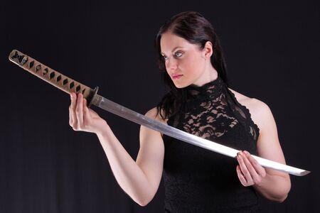 Young woman holding a samurai sword, katana, against black photo
