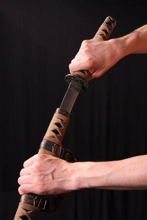 Closeup of man holding samurai sword in dramatic studio light photo
