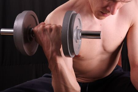 Man training with weight in dramatic studio light photo