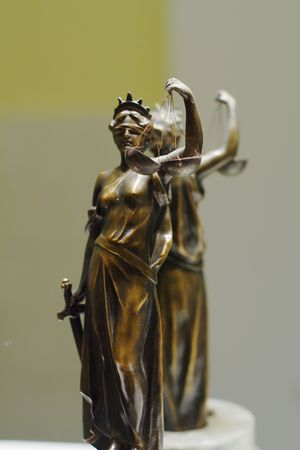 justness: Old bronze statue of Justice in front of mirror