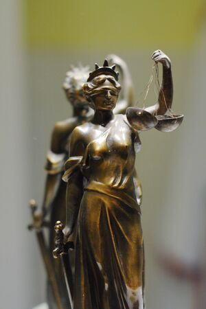 advocate: Old bronze statue of Justice in front of mirror